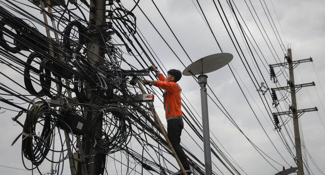 Worker Suddenly Realizes Untangling the Overhead Street Cables in the Thai Capital Will Take Longer Than He Thought