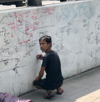 Homeless Man Caught in the Act of Scribbling Illuminati Conspiracies on Ratchathewi Bridge