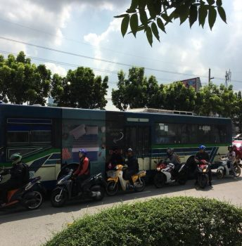 Motorcyclists Find Relief from the Sun Alongside Public Bus on a Hot Day in the Thai Capital